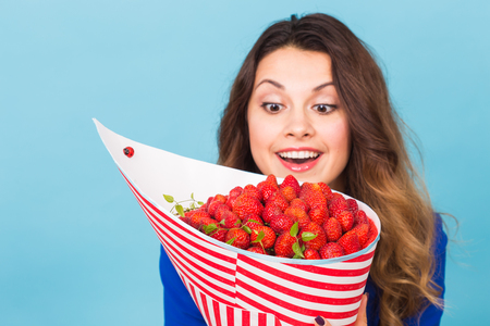 Close up of young woman with a bouquet of strawberry Standard-Bild