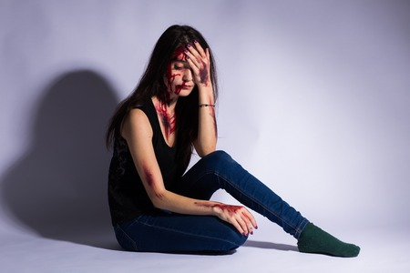 Rape battered bloody victim sad woman sits on the floor of a dark tunnel. Sexual assault concept real people. copy space Stock Photo