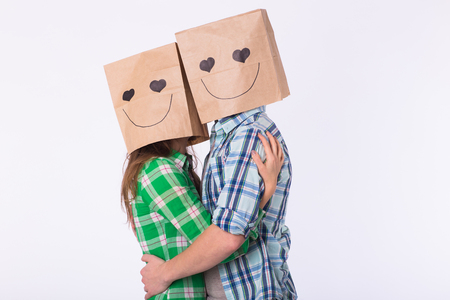 Love couple covering their faces with paper bag over white background Standard-Bild