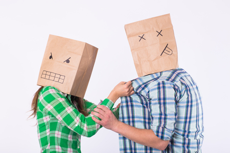 Violence against man. Aggressive woman with bag on head beating her man. Negative relations in partnership.
