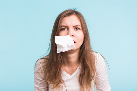 Young woman has a runny nose on blue background Stock Photo