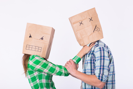 Violence against man. Aggressive woman with bag on head beating her man. Negative relations in partnership 版權商用圖片