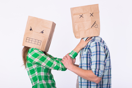 Violence against man. Aggressive woman with bag on head beating her man. Negative relations in partnership Stock Photo