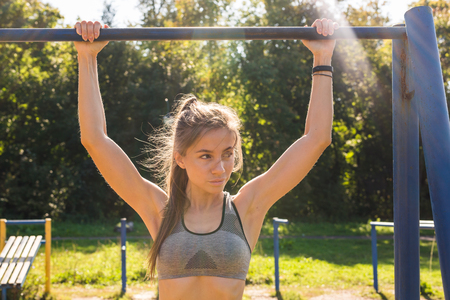 Active and young woman doing pullups. Stock Photo