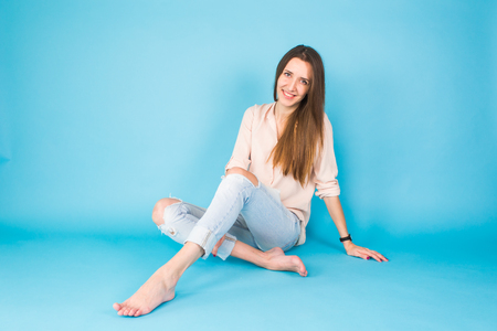 Hipster girl sitting on floor against blue background