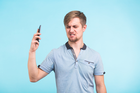 Handsome man with a tired and irritated look takes the phone away from her ear trying to move away from the complaints of an obsessive and annoying people Stock Photo