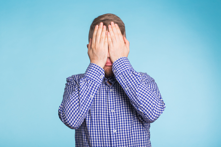 man covered his face with hand on blue background