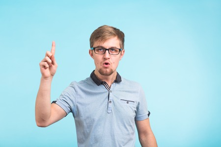 Wow, I understand it. Surprised young male raises finger as remembers something, isolated over blue background. Reaction and people