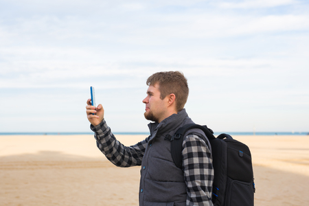 Traveler man taking photos to the beach with smartphone camera on summer travel vacation or hike to the coast. 版權商用圖片