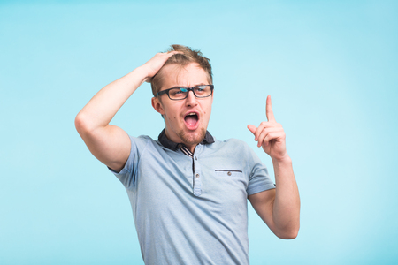 Closeup portrait of shocked stunned surprised young man eyes and mouth wide open, hands in air yelling screaming shouting on blue background. Negative emotion facial expression feeling