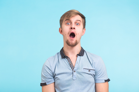 Closeup portrait of shocked stunned surprised young man eyes and mouth wide open on blue background. Emotion facial expression concept Stock Photo