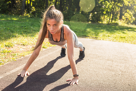 Fitness woman doing push-ups during outdoor cross training workout. Beautiful young and fit fitness sport model training outside in park
