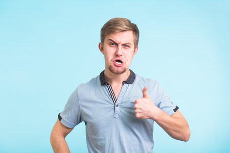 Funny angry man showing thumbs up on blue background