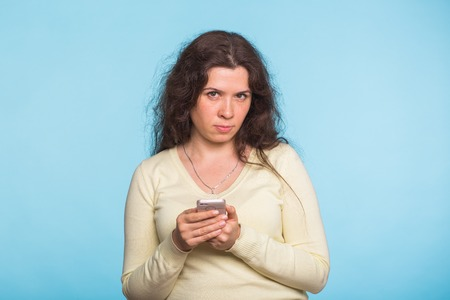 Angry and resentful woman waiting for excuses and explanations and is reproachfully looking isolated on blue background.