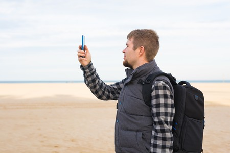 Traveler man taking photos to the beach with smartphone camera on summer travel vacation or hike to the coast. Standard-Bild