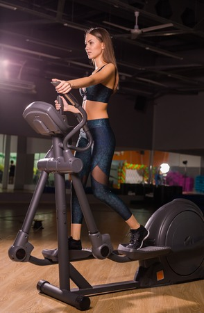 Beautiful woman at the gym exercising on a machine.