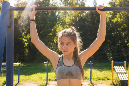 young athletic fitness woman working out at outdoor gym doing pull ups at sunrise.