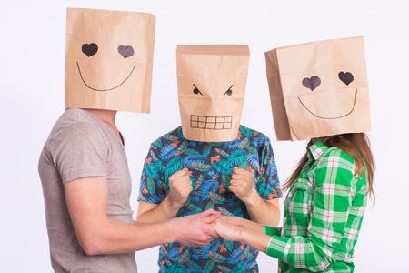 Triángulo amoroso, celos y concepto de amor no correspondido: mujer y hombre con bolsas sobre la cabeza tomados de la mano y otro hombre está enojado. Foto de archivo