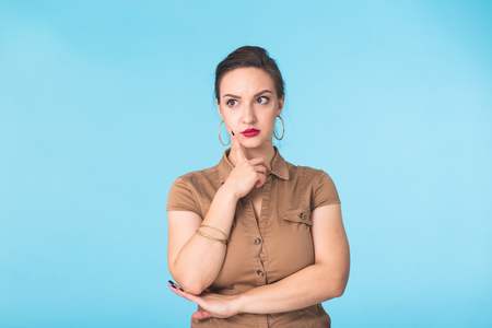 Concerned young woman on blue background