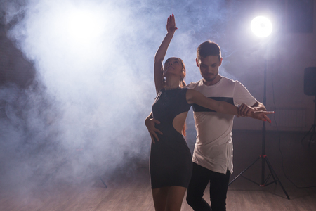 Active happy adults dancing bachata together in dance class Stock Photo