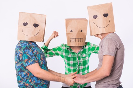 Love triangle, jealousy and homosexuality concept - gays with bags over heads holding hands and another woman is angry.