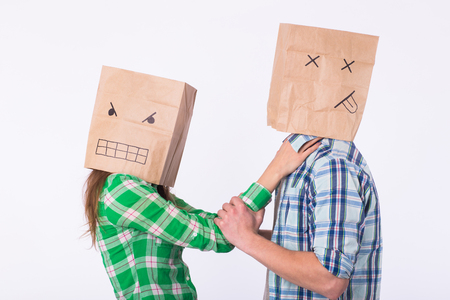 Violence against man. Aggressive woman with bag on head strangling her man. Negative relations in partnership. Stock Photo