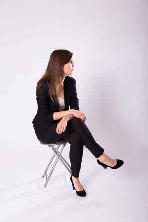 beautiful young business woman in black suit sits on a chair on white background