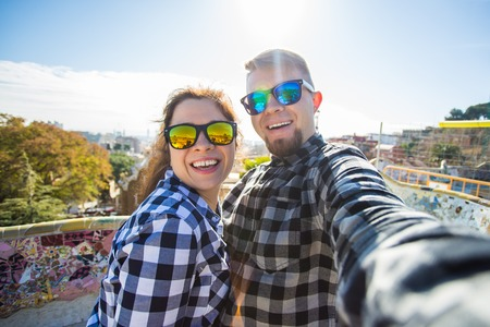 Travel couple happy making selfie portrait with smartphone in Park Guell, Barcelona, Spain. Beautiful young couple looking at camera taking photo with smart phone smiling in love 写真素材