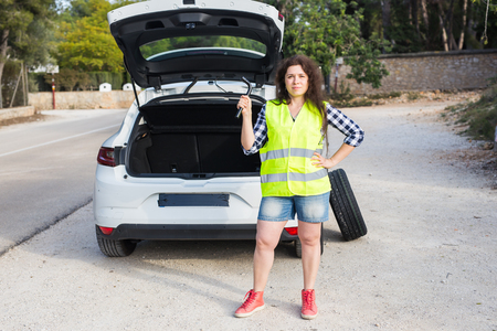 Broken down car. Woman standing alongside her broken down car on the road waiting for emergancy assistance Stock Photo