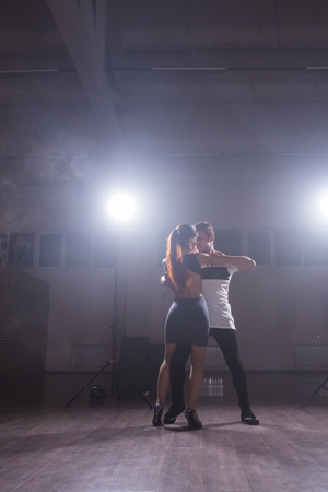 Skillful dancers performing in the dark room under the concert light and smoke. Sensual couple performing an artistic and emotional contemporary dance
