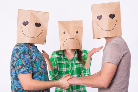Love triangle, jealousy and homosexuality concept - gays with bags over heads holding hands and another woman in confusion.