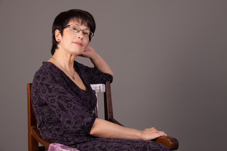 Elegant middle aged woman posing in studio