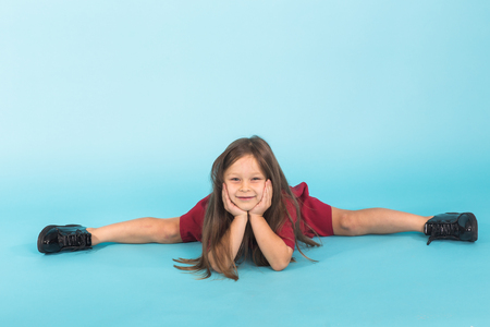 portrait of cute little ballerina doing splits isolated on blue background Stock Photo