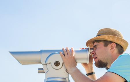 Man in the hat looking telescope