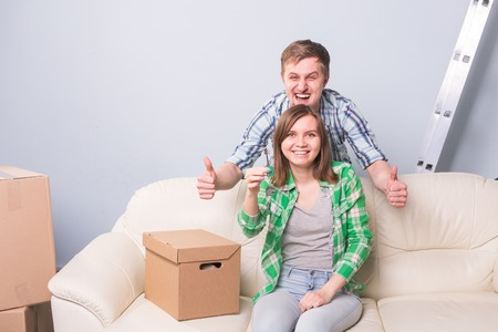 Young married couple with boxes and holding flat keys.