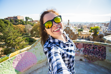 Young happy woman making selfie portrait with smartphone in Park Guell, Barcelona, Spain. Beautiful girl looking at camera taking photo with smart phone smiling 写真素材