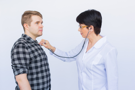 healthcare, medical exam, people and medicine concept - young man and doctor with stethoscope listening to heartbeat over white background Stock Photo
