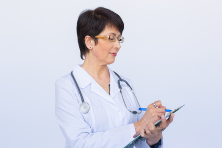 Portrait Of Female Doctor Writing On Clipboard Over a white background