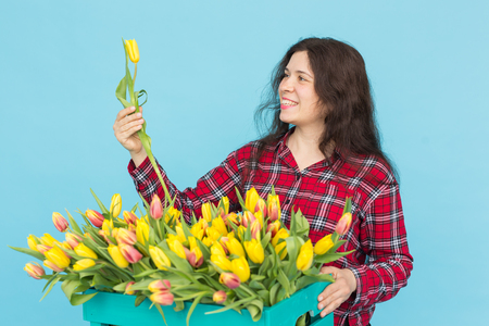 Charming female florist sorts out tulips in the box, selects them for the future flower arrangement Banco de Imagens