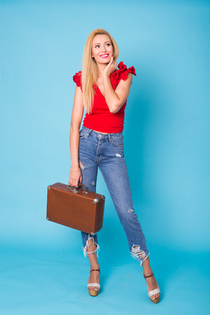 Summer, travel and vacation concept - Portrait of a beautiful young blonde woman with retro suitcase on blue background.