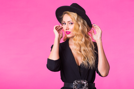 Gorgeous young blonde woman in black stylish fashionable hat posing on pink background.