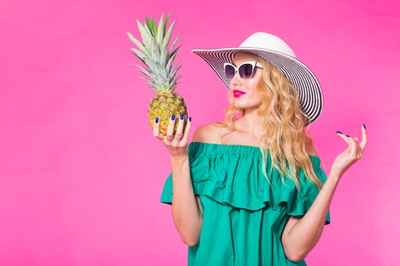 Happy young woman holding a pineapple on a pink background. Summer, diet and holidays concept Stock Photo