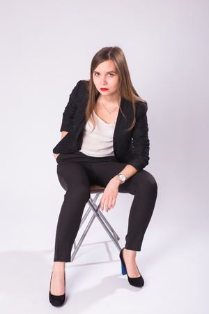 Full length studio portrait of young business woman in black suit, high heel shoes, sitting in chair on white background Stock Photo