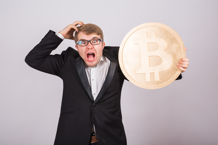 Portrait of a screaming businessman holds big golden bitcoin in his arms. Man in panic of cryptocurrency crash