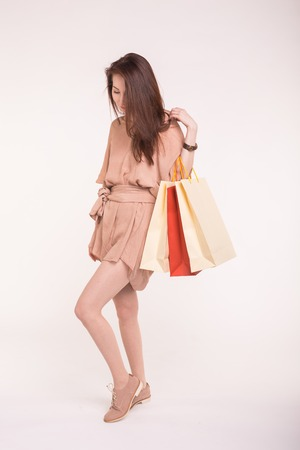 Portrait of young happy smiling asian woman with shopping bags on white background