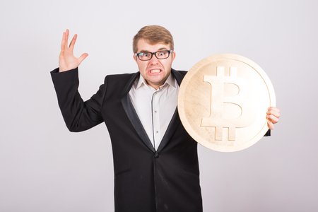 Portrait of a screaming businessman holds big golden bitcoin in his arms. Man in panic of cryptocurrency crash 写真素材 - 102080338