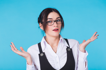 Surprised young woman shouting over blue background. Looking at camera Stock Photo