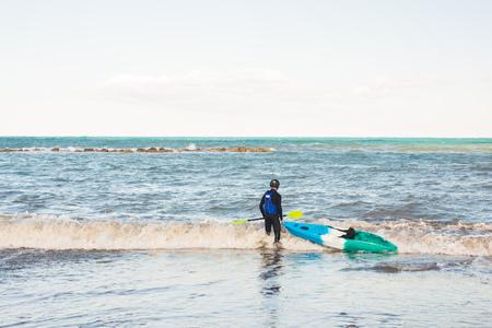Man holding kayak oar against the sea