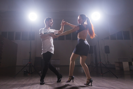 Active happy adults dancing bachata together in dance class Foto de archivo