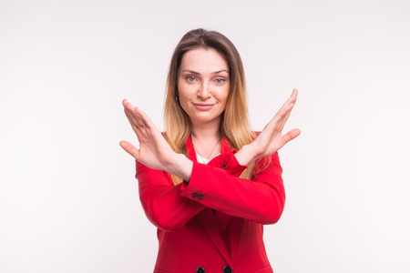 Portrait of young european woman in red jacked in studio with crossed hands.